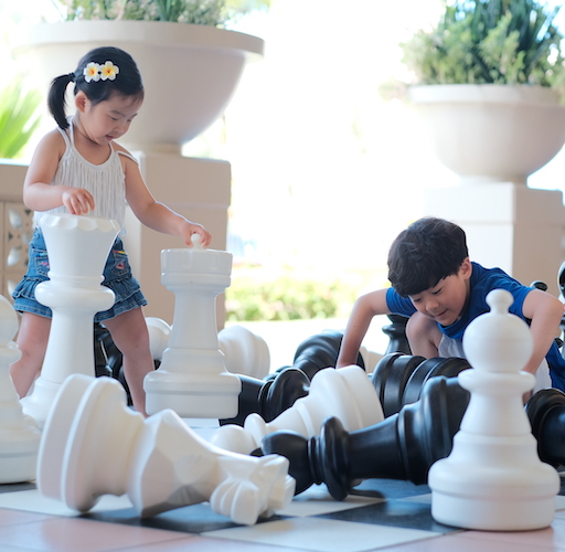 Kids are playing oversized chess