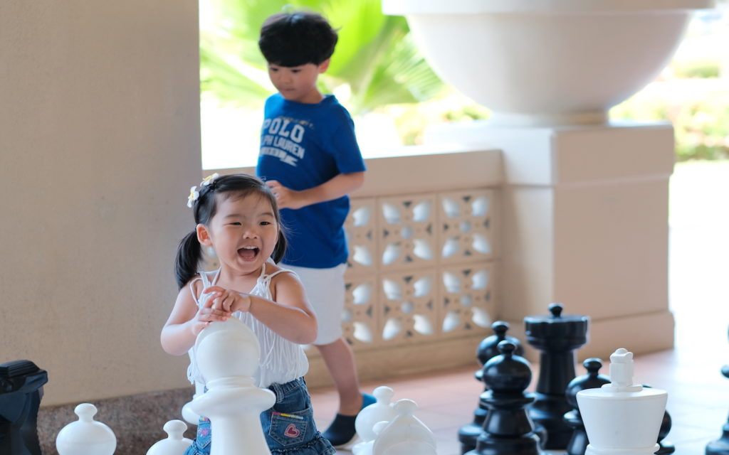Kids are smiling and playing with oversized chess