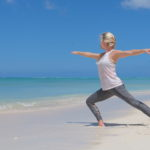 A woman is practicing Tai Chi at the beach