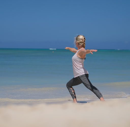 A woman is exercising by the beach